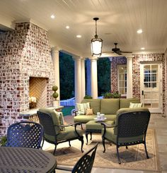 Covered back porch with columns, fireplace, nice lighting details, stone floor