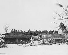 American tanks and armored gun carriers drive over snow-covered terrain to Samree during Battle of the Bulge. Capture of the city opened the way to Houffallize, heart of the Bulge.