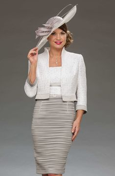This short dress has a square neckline and a capped sleeve. The bust fabric has a subtle sparkle. This same fabric is used for the matching jacket. Colours: Silver/ivory, navy