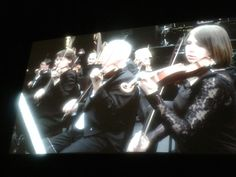 At the launch night of the Philharmonia's 'Universe of Sound' installation at Augustine House, Canterbury. Large screens depict the various sections of the orchestra at work as visitors move around the exhibition.