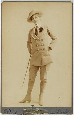 Jane Renouardt en pied, habillée en costume d'homme et cravache à la main droite. ca. 1910