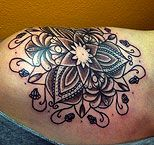 Lotus tattoo on a woman's shoulder (black)