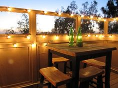 Oversized Christmas lights make this balcony an intimate nighttime dining area.