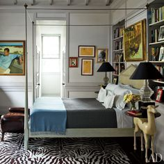 An eclectic master bedroom with traditional architecture featuring a four poster bed and built-in bookshelves | archdigest.com