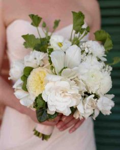 This white bundle of gardenias, garden roses, geranium, allium, ranunculus, and tulips pops against the bride's blush wedding gown.