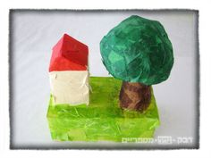 little house and a tree made out of recyclables covered with masking tape and tissue paper