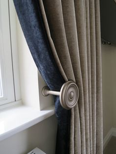 Wooden holdback draws the curtain away from the window to maximise light. The taupe velvet curtain has a dark blue leafing edge as a contrast.