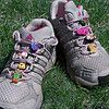 Gray & pink running shoes with eight clear Flibbers™ shoelace charm adapter clips and eight Jibbitz rubber clog charms: flip-flops, a breast cancer ribbon, a cat, a turtle, a Croc clog, a monkey, and two monsters   collection of running shoes