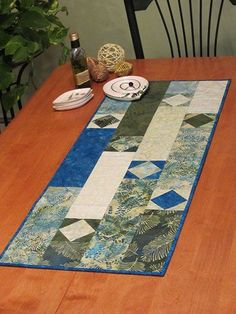 "Using just 8 fat eighths or fat quarters, you can create this lovely diamond-patterned runner. Contrast your light and dark fabrics for added interest. Learn to make square in square blocks using an easy technique, and pair them with simple strip-piecing. The finished result is equally as lovely in batiks, traditional or modern prints. Size: 17"" x 42"". Skill Level: Easy"