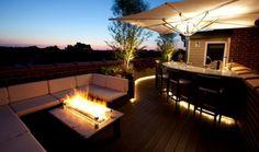 canapé d'angle blanc et foyer à feu ouvert dans le jardin moderne