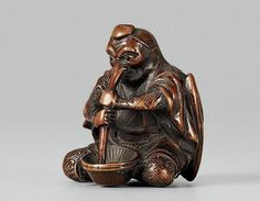 A boxwood netsuke of a long-nosed tengu. First half 19th century. The tengu dressed as a yamabushi and with huge crow's wing at his back sits in front of a ribbed mortar (suribachi) using his long nose as a pestle (surikogi). Eyes of bone and black horn.Grinding in a mortar is a sexual allusion.