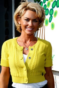 Kelly Carlson short curly hair.  Apply a volumizing and curl-enhancing product. Blow dry the hair using a round hair brush. Set the hair in hot rollers of various sizes all over. To create height in the crown area, add a little back combing in the area, smoothing over the top part. Complete the look with a finishing spray.