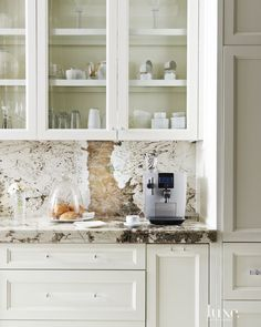 In the kitchen, striking Brazilian granite from Arizona Tile sheaths the backsplash, countertops and island. Cabinetry from R & G Custom Crafting boasts a painted ivory finish and features Lucite pulls from Central Arizona Supply.