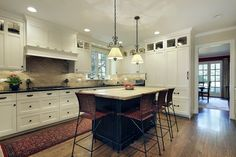 Simple design features add spice to this kitchen - namely wicker stools, burgundy runner and brick pattern back splash.
