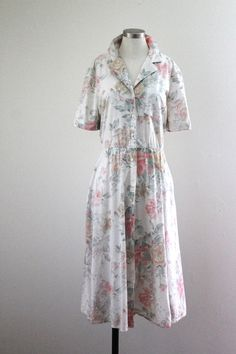 Vintage 1990s dreamy floral shirtdress. Beautiful watercolor floral, this dress buttons up the front but also has an elastic waist and belt-loops for a 1950s style. Excellent vintage condition. Interior tag reads R.E.O. Originals size 10. MEASUREMENTS  Bust: 42 Waist: 36-40 stretched Hips: Open Length: 29  All waist, bust, and shoulder measurements are taken flat and doubled.