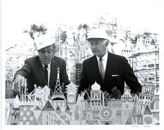 This black-and-white photograph shows Walt Disney and Louis Lundburg studying the Imagineers' model of It's a Small World at Disneyland circa 1966 during the attraction's installation in Fantasyland. Moved from the 1964–65 New York World's Fair, the facade of It's a Small World is seen shrouded in scaffolding behind the two men. Mr. Lundburg was Chairman of Bank of America, the corporate sponsor at Disneyland.