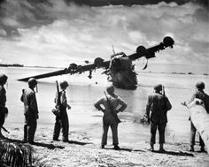 """A destroyed Japanese H8K flying boat is examined by men of the US Army - October 24, 1943 [[MORE]] """" A Kawanishi H8K Type 2 Nishiki Daitei (Large Flying Boat) on Yellow Beach near King's Wharf is examined by men of the US Army's 165th Infantry..."""
