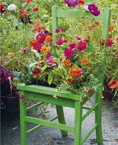 Flowers planted into the seat of a vintage chair.The combination of hot summery red and orange flowers with the bright emerald green chair is fab