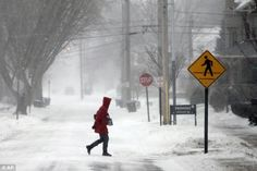 Biting: A woman crosses a street in Bowling Green, Ohio Thursday as a winter weather advisory is in effect