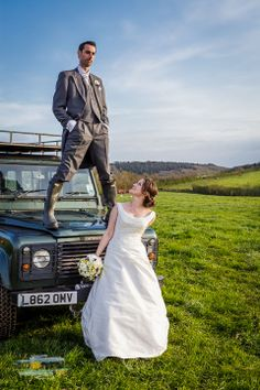 Groom in Wellies standing on a Landrover Photography by http://weddings.devon.photography