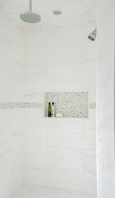 Chic walk-in shower features white marble grid tiles accented with gray mosaic border tiles fitted with a tiled niche as well as two shower heads.