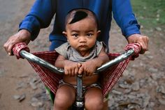Photo taken by @stevemccurryofficial // I photographed this little boy in a bicycle sling and his father at Banteay Srei Angkor Cambodia. The way the child is gripping the handlebars mirrors his fathers' hands.  Check out our current project in Afghanistan: @imagine_asia by natgeo