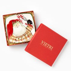 The Old St. Nick Square Canape Plate from VIETRI's boxed gift collection is presented in a red pinstripe box and nestled in rustic straw. The plate, painted in classic holiday colors of red, green and white, shows old St. Nick with a sprig of holly.
