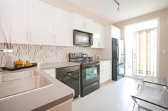 l shaped open concept kitchen with white flat panel cabinetry black appliances tile