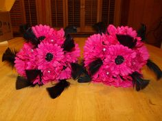 Hot pink Gerber daisies with black glitter centers and black feathers at www.silkweddingflowersforless.com