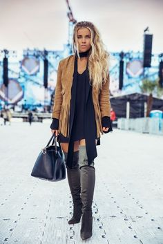 Tan suede fringed jacket over black dress with gray OTK boots.