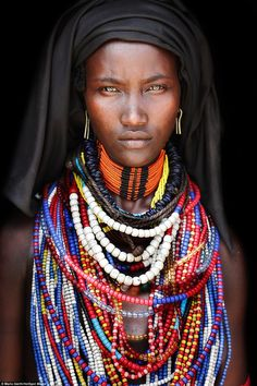 Women from the Arbore tribe cover their heads with black cloths but are known for their love of colourful necklaces and earrings