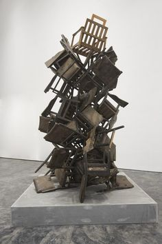 Mansoor Ali - Dance Of Democracy  Ali's free-standing installation of discarded chairs piled high, without direction or reason, balances precariously and may at any moment fall to the ground. Ali often employs ready-made objects such as the chairs used in this work, which are wrecked and battered in their appearance. Rising from its elevated base, Dance of Democracy appears to stay upright by sheer luck, infusing his art with humour and poignancy.