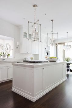 A white kitchen island boasting a light gray quartz countertop is fitted with an integrated gas cooktop lit by two Two Hudson Valley Lighting Alpine Pendants.