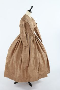 A golden-brown silk dress, circa 1840. rows of small silk wrapped buttons outline the V shaped pleats to the waist, front skirt panels, and bows to upper sleeves, pocket concealed within front seam