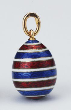 Fabergé miniature egg pendant by workmaster Erik August Kollin, before 1886. Provenance: Probably acquired by Queen Alexandra; in the Royal Collection by 1953. Easter egg pendant with concentric circle bands of incised scrolls and scallops decorated in blue and red enamel with white enamelled lines in between.