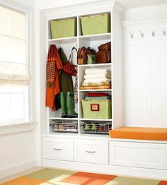 Ready-to-assemble base drawers, locker-style cabinets, and a partial wall with hooks enhance the style of the space, while bins, boxes, and slide-out wire drawers boost function. Baseboards and crown molding seamlessly integrate the cabinetry with the walls. Cushioned bench seating on the base cabinets creates a perch for dressing.