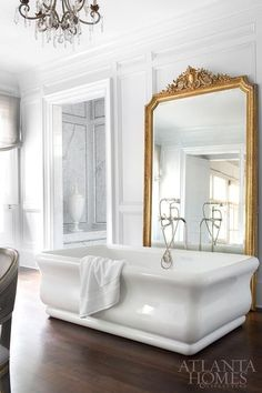 Stately light gray bathroom boasts a freestanding bathtub positioned on wood floors in front of a large gold leaf baroque mirror that leans against walls and decorative moldings painted Sherwin Williams Bunny Gray.