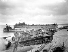 A pair of M10 tank destroyere come ashore during training exercises in preparation for D-Day, with an LST in the background. England, 1944. [3,259x2,480]