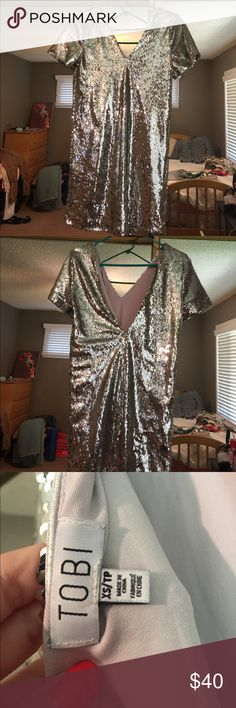 Glitter sequence silver dress from Tobi!! Extremely cute sequence dress, inside is a soft lining so you don't the sequence at all! Back of the dress is a low cute v , very flattering! Message for any questions size is xs but can definitely fit small. Only worn once! Tobi Dresses Midi
