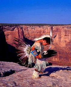 Young Native American doing a dance on the edge of a cliff