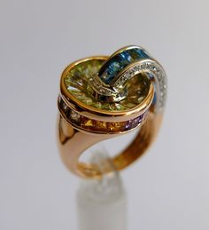 It features a curving arc of Swiss blue topaz that descends into a pool of peridot, with baguettes of citrine, iolite, blue topaz, amethyst and rhodolite garnet set into the side gallery