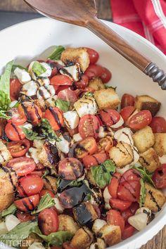 Caprese Panzanella Salad, grape tomatoes, fresh mozzarella, and basil tossed with homemade parmesan croutons!