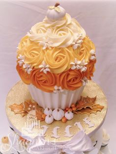 Giant smash cupcake decorated for fall with orange ombre rosettes, and white and gold accents. Pumpkins and autumn leaves add detail.