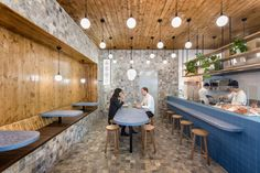 Sans-Arc Studio has used blue terrazzo, mottled grey travertine and stained wood to evoke a subtle seaside experience for diners at this Adelaide chip shop with a Japanese twist.