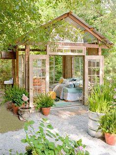 chalet de jardin habitable aménagé avec un lit et un tapis et doté de plusieurs fenêtres