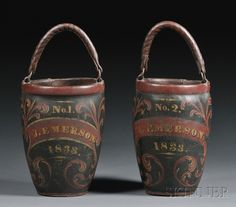 """Pair of Painted Leather Fire Buckets, America, c. 1833, painted dark green with red and gilt accents, with inscriptions """"No.1"""" and """"No. 2"""" over the name """"J. EMERSON"""" and date """"1833,"""" with leather handles, (paint losses), ht. to top of rim 12 1/4, to top of upright handles 18 1/2 in."""