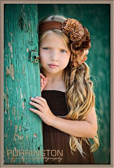 Love the colors! Beautiful young girl behind turquoise green weathered door with a variety of brown flowers in her headband with long blonde curly curled hair.