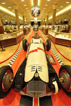 A historic Indy 500 race car sits in the main aisle at Macy's Herald Square in NYC.
