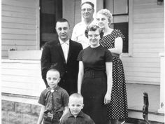4/21/1959 — Capt. Virgil Gus Grissom, one of the hot jet pilots nominated to man a satellite, slowed down for this family picture during an unannounced visit to his home town. Grissom and his wife, Betty, stand behind their sons, Scott, 9, and Mark, 4. In back are his parents Dennis Grissom and Cecil Grissom.