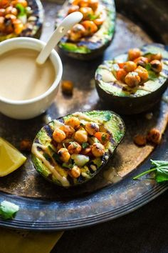Grilled avocado is stuffed with a fresh mixture of cucumber, tomato and crispy grilled chickpeas! A drizzle of tahini makes this a delicious, vegan dinner!